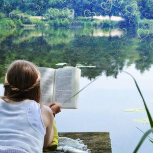 Lesbische Frau liegt am See und liest